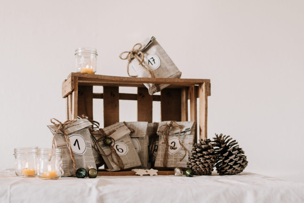 Upcycling DIY Adventskalender selber machen: Papiertüten aus alten Zeitungen basteln, Zahlen darauf schreiben und Geschenke darin verpacken